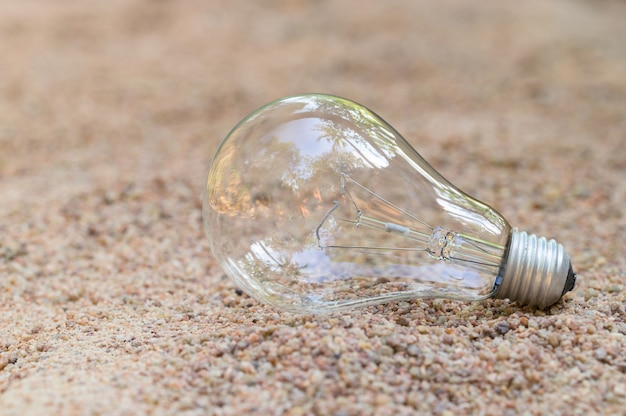 Лампочка пуста на песке. энергетическая концепция