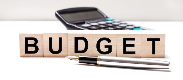 На светлом столе есть черный калькулятор, перьевая ручка и деревянные кубики с текстом бюджет. бизнес-концепция
