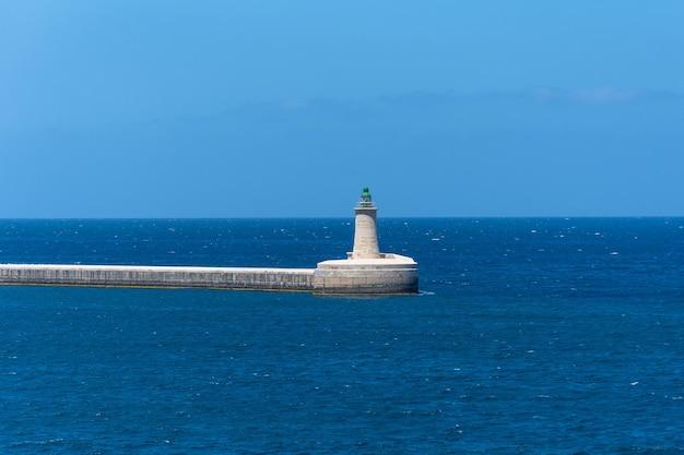 Маяк на каменном мысе в хорошую погоду на средиземном море.