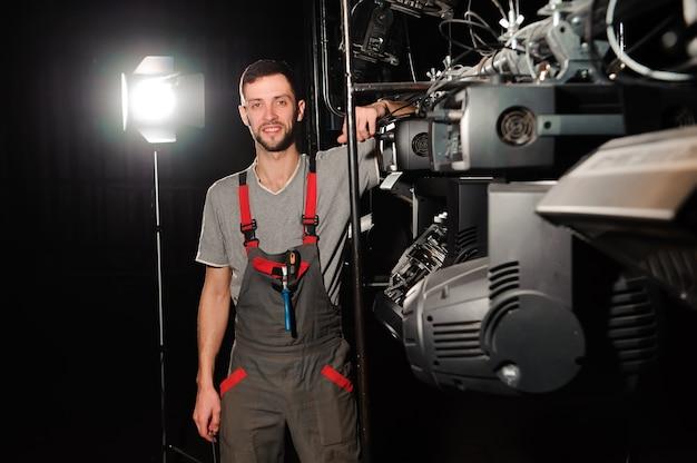 Инженер по свету ремонтирует световое устройство на сцене.