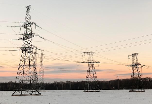Линия высоковольтной передачи в зимнее время года. фотография сделана на закате