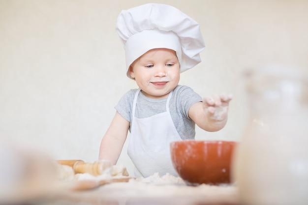 料理人のスーツを着た小さな男の子が生地を彫刻します小さな子供のスカリオンがシェフのスーツで夕食を作ります