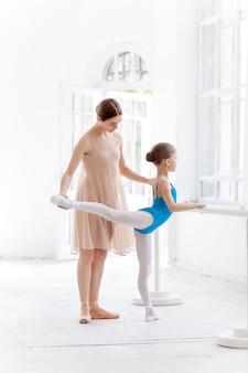 댄스 스튜디오에서 개인 교사와 함께 발레 바레에서 포즈를 취하는 작은 발레리나