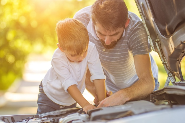 Маленький мальчик и отец ремонтируют машину
