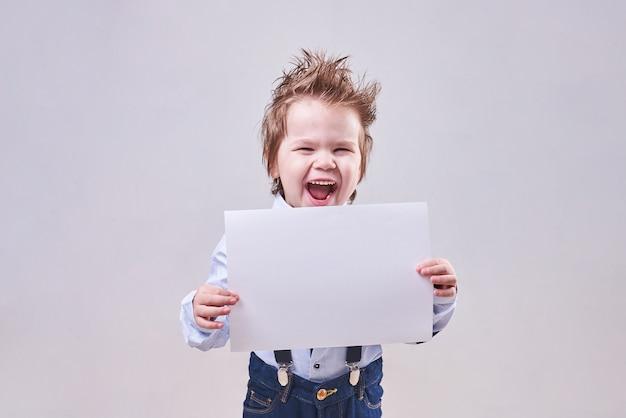 Маленький мальчик держит в руке чистый лист бумаги