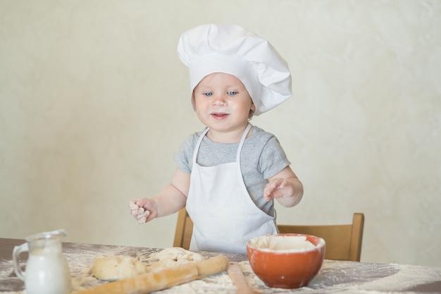 料理人のスーツを着た小さな男の子が生地を彫刻します。赤ちゃんはシェフのスーツで夕食を作る