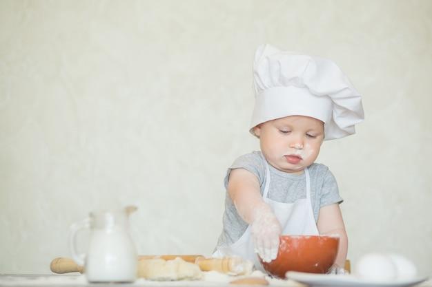 料理人のスーツを着た小さな男の子が生地を彫刻します。ベビースカリオンはシェフのスーツで夕食を作ります。料理のコンセプト