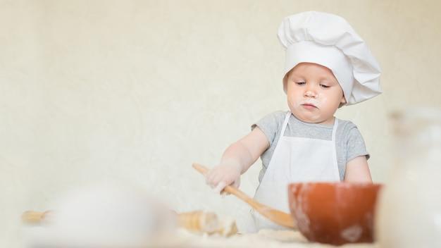 料理人のスーツを着た小さな男の子が生地を彫刻します赤ちゃんのスカリオンがシェフのスーツで夕食を作ります