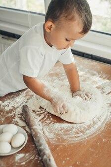 Маленький мальчик на кухне сам в белой футболке крепко месит тесто