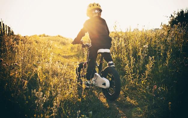 Вечером маленький мальчик едет на велосипеде по проселочной дороге