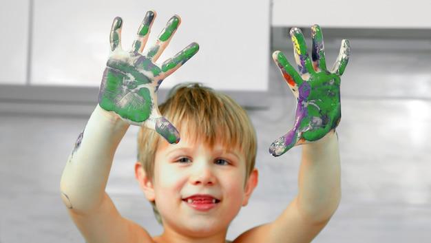 어린 소년의 더러워진 손에 물감이 묻습니다. 어린이 발달의 예술적 창의성
