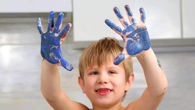어린 소년의 더러워진 손에 페인트