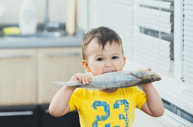 小さな男の子は、川で釣った大きな魚を見せてくれます。有機食品の概念。