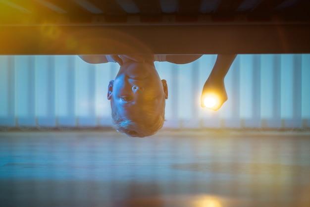 침대 밑에 손전등이 있는 어린 소년. 밤 시간