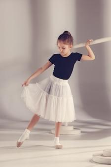 발레 랙 근처 회색 배경에 스튜디오에서 포즈 발레리나 댄서로 어린 소녀