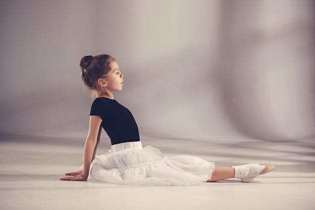 Маленькая девочка как танцор балерина, сидя в студии на сером фоне. мечты о балетных концепциях