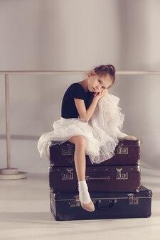 회색 배경에 가방에 스튜디오에 앉아 발레리나 댄서로 어린 소녀. 발레 개념에 대한 꿈