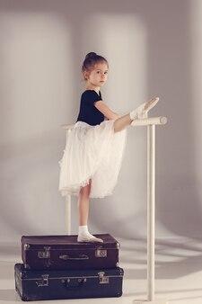 회색 배경에 가방에 스튜디오에 서 있는 발레리나 댄서로 어린 소녀. 발레 개념에 대한 꿈