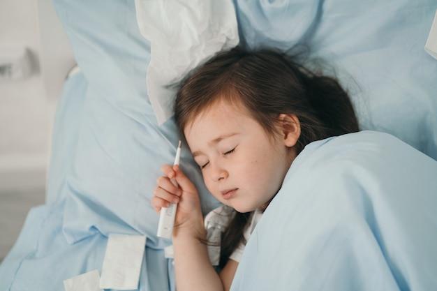 その少女は風邪を引いた。子供たちはハンカチにくしゃみをします。子供は病気で、家で治療を受けています。子供の季節風邪。
