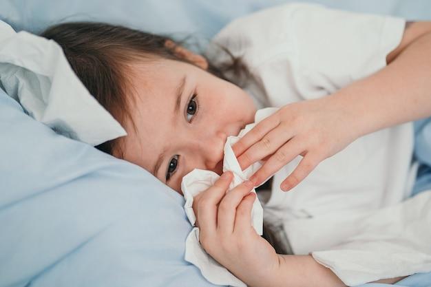 Маленькая девочка простудилась. дети чихают в платок. ребенок болен, лечится дома. сезонные простуды у детей.