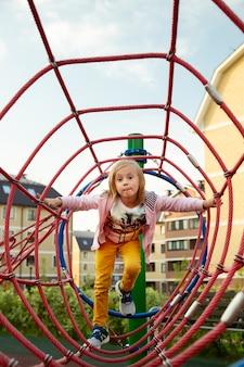 少女は遊び場でロープを登る