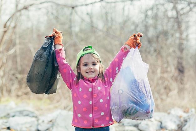 어린 소녀는 숲과 공원에서 쓰레기 두 봉지와 플라스틱 병을 모았습니다. 소녀는 자원 봉사자들이 공원을 청소하는 것을 도운 것을 기쁘게 생각합니다