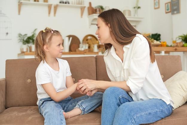 어린 소녀는 어머니에게 불평하며 웁니다. 소파에서 딸을 진정시키는 젊은 여성