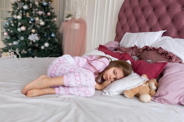 Маленькая девочка не хочет ложиться спать в рождественскую ночь. рождественская сказка. волшебные моменты счастливого детства.
