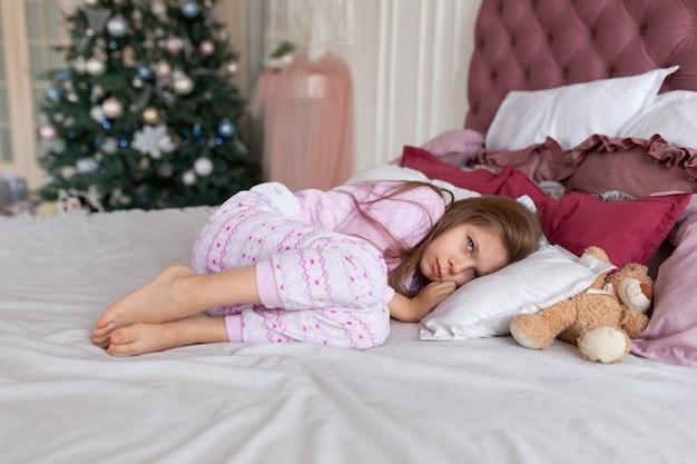 어린 소녀는 크리스마스 밤에 잠자리에 들기를 원하지 않습니다.