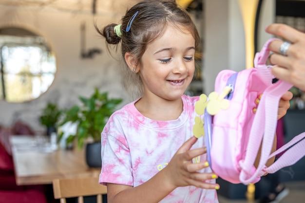 Маленькая девочка осматривает подаренный ей рюкзак.