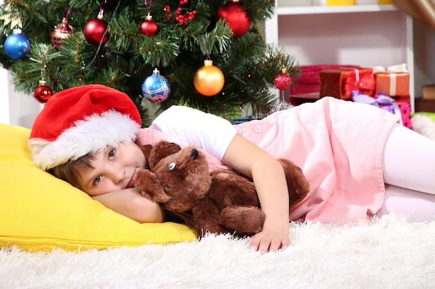 小さな女の子は、お祝いに飾られた部屋で彼らの手に贈り物を持って眠りに落ちました