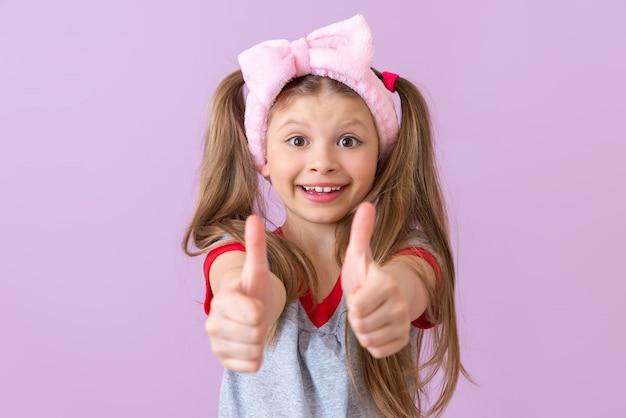 어린 소녀는 매우 놀란 엄지 손가락을 치켜 든다. 전부다 괜찮아.