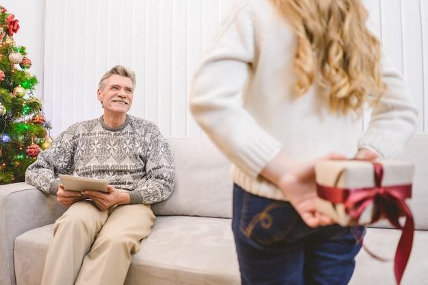 少女は幸せな祖父のためのギフトボックスを保持します