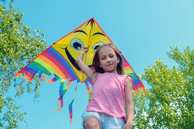 어린 소녀는 밝은 연을 손에 들고 푸른 하늘을 배경으로 미소를 짓고 있습니다. 여름, 자유, 행복한 어린 시절의 개념.