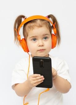 Маленькая девочка в наушниках. девушка слушает музыку. маленькая девочка играет в телефон на заднем плане