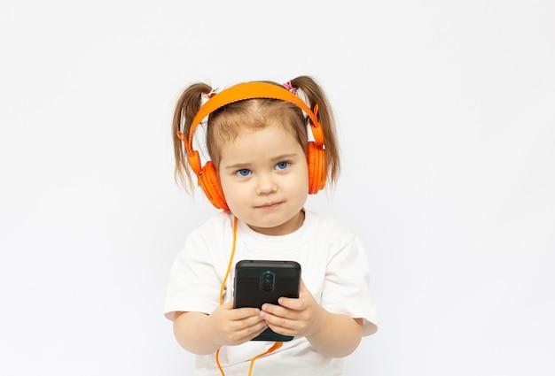 헤드폰에있는 어린 소녀. 여자 아이가 음악을 듣고 있어요. 어린 소녀는 배경에서 전화를 재생