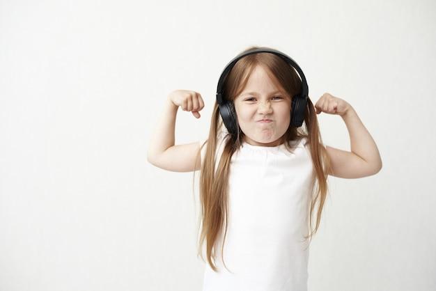 헤드폰에서 어린 소녀입니다. 어린 소녀가 찡그린 다. 근육을 가진 어린 소녀