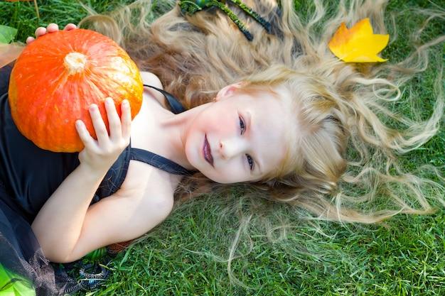 少女は魔女の衣装、黒い口紅を着ています。かぼちゃ。ハロウィーン。秋。 10月
