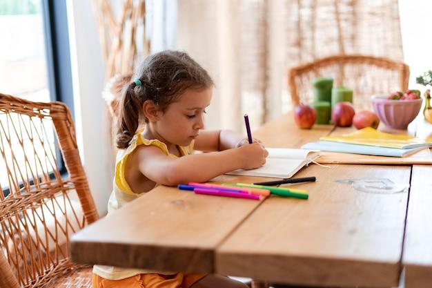Маленькая девочка занимается дошкольными занятиями, она сидит за большим столом, на котором лежат фрукты и тетради, девочка учится писать в тетрадь цветными фломастерами.