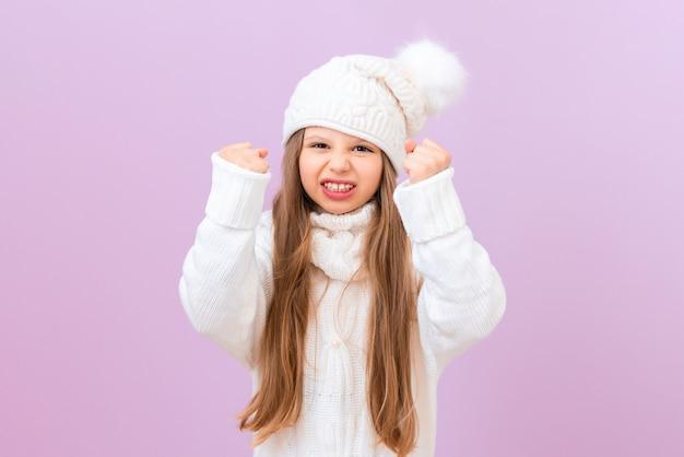 어린 소녀는 매우 화가 난다. 겨울 따뜻한 모자 소녀입니다.