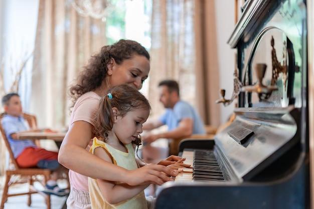 Маленькая девочка учится мастерски играть на пианино, внимательно слушает указания воспитателя и старается все делать правильно.