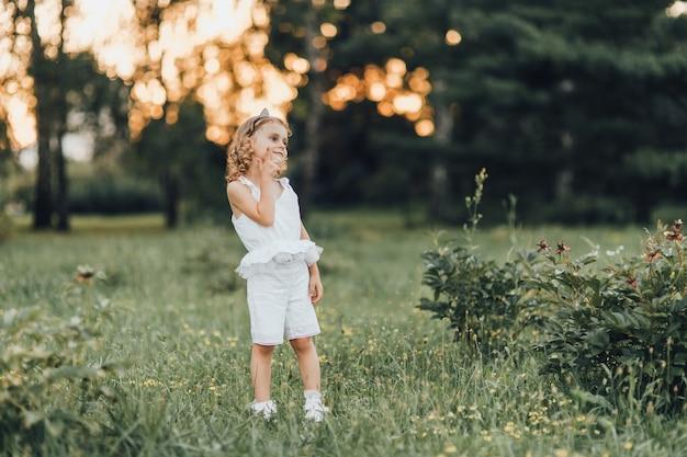 少女は日没時に公園で美しく見えます