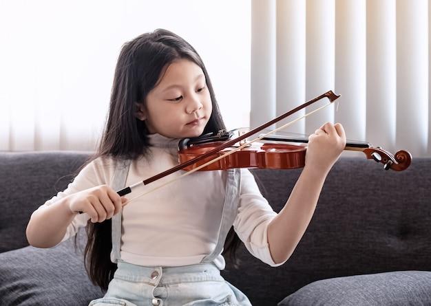 행복 한 느낌으로 스튜디오 음악실에서 바이올린을 연주하는 어린 소녀