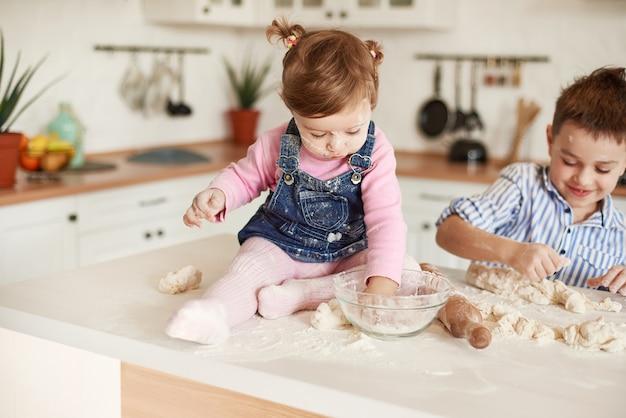 小さな女の子は小麦粉の入った皿に手を入れ、背景の男の子は生地をこねます