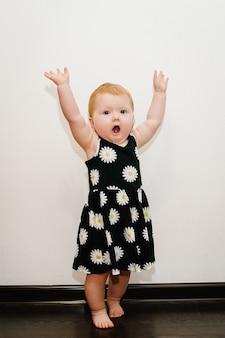 Маленькая девочка показывает, какая она большая, подняла руки на белой поверхности в комнате.