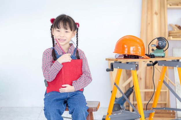 喜んで微笑んだ少女は、木造の店で本と鉛筆を手に持っています。