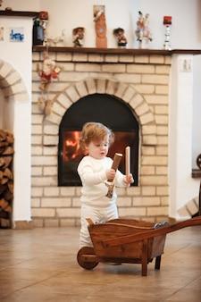Маленькая девочка стоит дома против камина