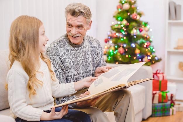 할아버지와 함께 어린 소녀는 크리스마스 트리 근처에서 사진 앨범을 본다