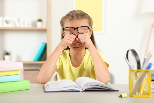 小さな女の子の目は子供の眼鏡の視力の問題で傷ついた