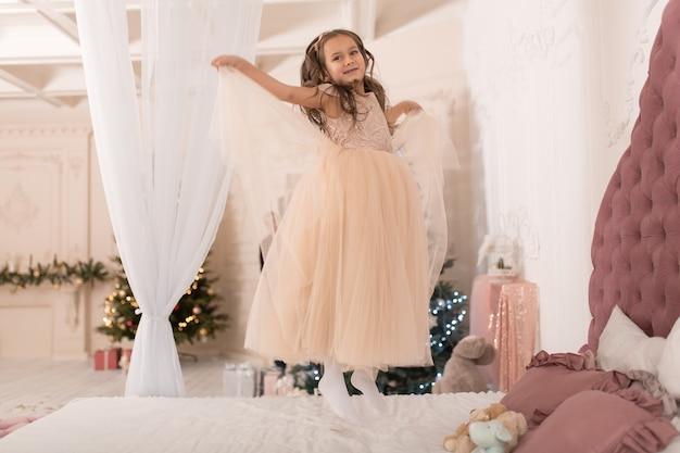 Маленькая принцесса прыгает на кровати.